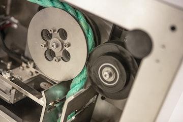 Nærbilde av mekanisme for å dra tau gjennom maskinen