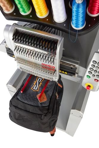 Melco EMT16 X broderingsmaskin med Melco Fast Clamp Pro med bag sett ovenfra